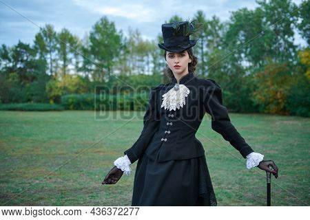 Fashion of the late 19th - early 20th century. A sophisticated brunette lady in a strict elegant black suit of the 19th century strolls through an autumn park.