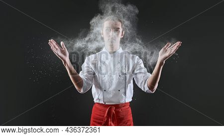 Professional male pastry chef prepares an exquisite dish with flour flying in the air in a restaurant kitchen. Food and meals.