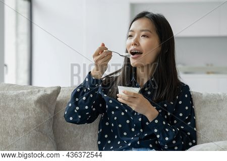 Young Asian Woman Eats Fresh Yogurt For Breakfast Sitting On The Couch