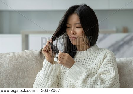 Asian Woman Sitting On The Couch With Hair Problems - Brittle, Damaged, Dry, Dirty And Falling Out H