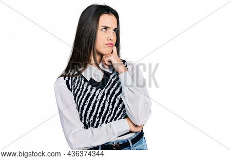 Young brunette teenager wearing casual elegant look thinking concentrated about doubt with finger on chin and looking up wondering