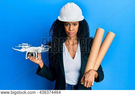 Middle age african american woman wearing safety helmet holding blueprints and drone skeptic and nervous, frowning upset because of problem. negative person.
