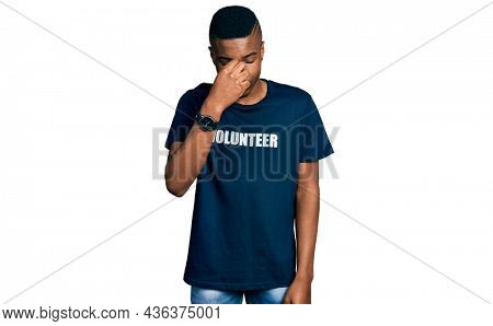Young african american man wearing volunteer t shirt tired rubbing nose and eyes feeling fatigue and headache. stress and frustration concept.