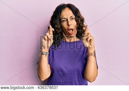 Middle age hispanic woman doing fingers crossed gesture in shock face, looking skeptical and sarcastic, surprised with open mouth