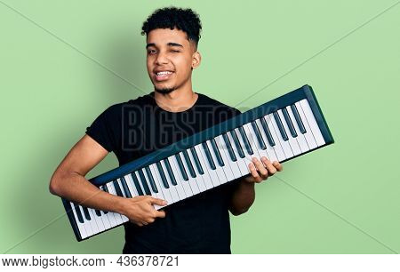 Young african american man holding piano keyboard winking looking at the camera with sexy expression, cheerful and happy face.