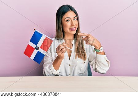 Young hispanic woman holding dominican republic flag sitting on the table smiling happy pointing with hand and finger
