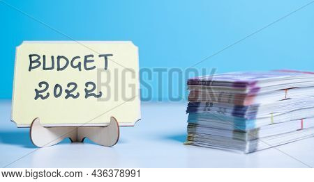 Concept Of Planning Or Setting Budget For New Year 2022 Showing By Stack Of Currency Notes Next To B