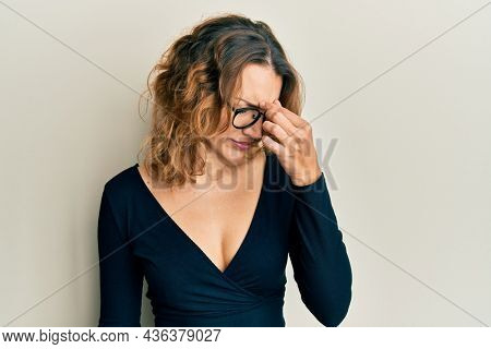Young caucasian woman wearing business shirt and glasses tired rubbing nose and eyes feeling fatigue and headache. stress and frustration concept.