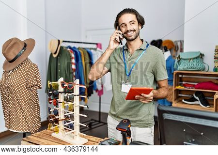 Handsome hispanic man working as shop assistance speaking on the phone at retail shop