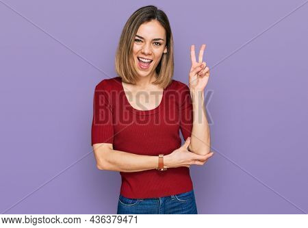 Young blonde girl wearing casual clothes smiling with happy face winking at the camera doing victory sign with fingers. number two.