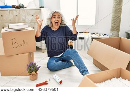 Middle age woman with grey hair sitting on the floor at new home celebrating victory with happy smile and winner expression with raised hands