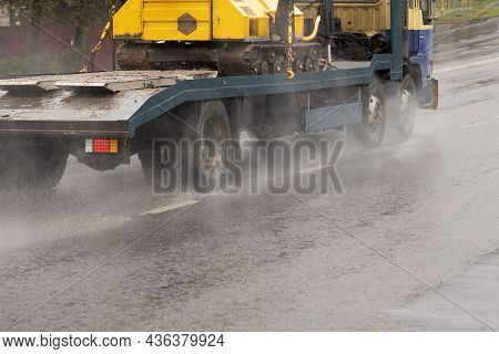 Short Flatbed Truck Carrying A Crawler Tractor On A Wet Road With Splashes During The Rainy Day
