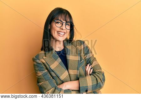 Young hispanic woman wearing business style and glasses happy face smiling with crossed arms looking at the camera. positive person.