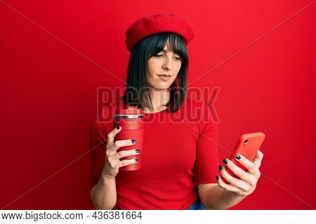 Young hispanic woman using smartphone and drinking a cup of coffee relaxed with serious expression on face. and natural looking at the camera.