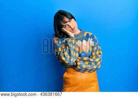 Young hispanic woman wearing casual winter sweater thinking looking tired and bored with depression problems with crossed arms.