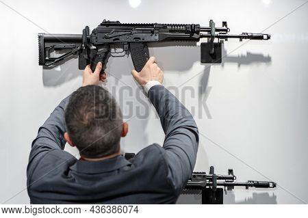A Man In A Shop Inspects A Firearm. Back View. Unrecognizable Face. Selective Focus