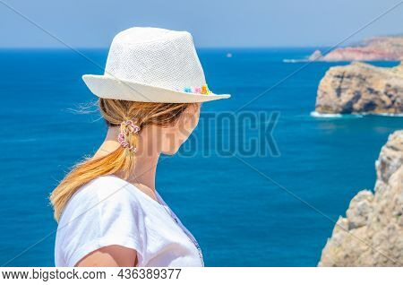 Young Woman Traveler With White Hat And Shirt Staying At Cabo De Sao Vicente Cape Saint Vincent