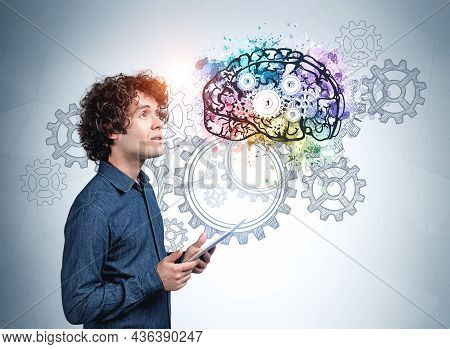 Young Man In Blue Shirt With A Pensive Look, Holding Device In Hands. Cogwheels And Gears On Blue Wa