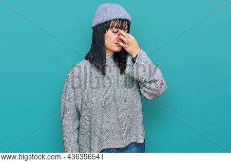 Young hispanic woman wearing cute wool cap tired rubbing nose and eyes feeling fatigue and headache. stress and frustration concept.