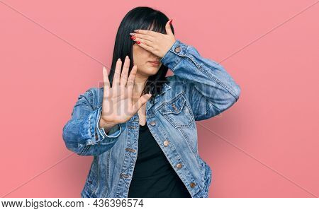 Young hispanic woman wearing casual clothes covering eyes with hands and doing stop gesture with sad and fear expression. embarrassed and negative concept.