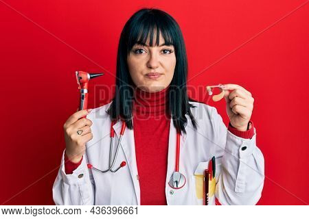 Young hispanic doctor woman holding deafness headset and otoscope relaxed with serious expression on face. simple and natural looking at the camera.