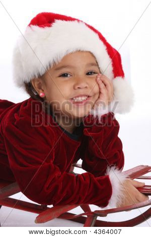 Girl In Santa Hat On A Sled