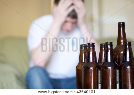 Man holds head with group of empty beer bottles