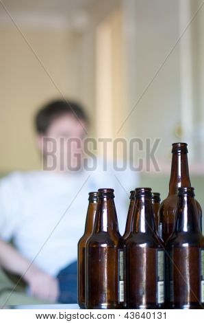 Vertical of man looking right, empty beer bottles