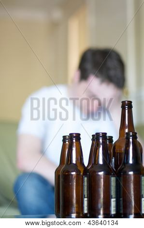 Vertical, man holding his head up with empty beer bottles