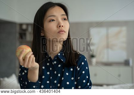 Thoughtful Asian Woman Holds An Apple In The Living Room And Looks Out The Window