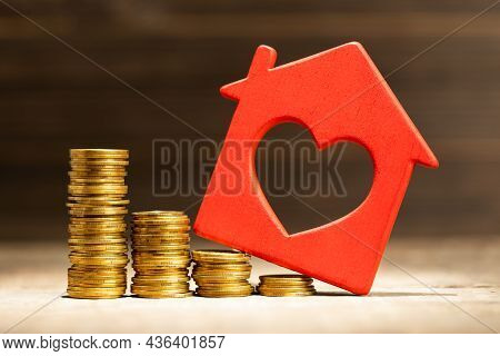 Steps Down From Coins And A Red House. House Price Falling Concept