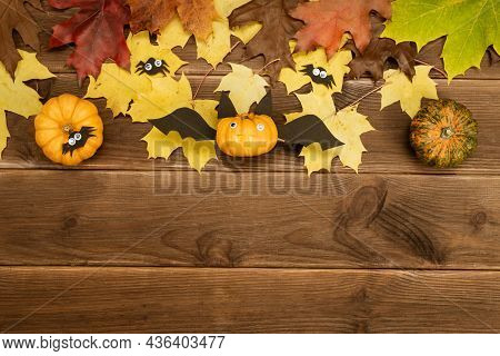Autumn Decor Of Pumpkin And Yellow Maple Leaves On A Wooden Background With Copy Space. Diy Pumpkin