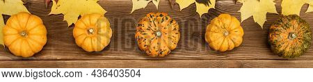 Autumn Decor Of Pumpkin And Yellow Maple Leaves On A Wooden Background. Halloween Decor