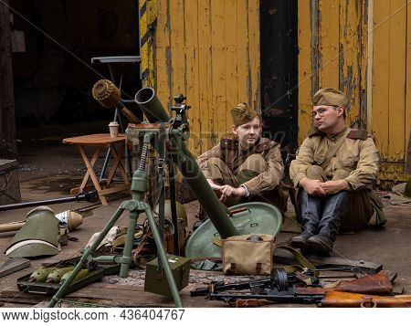 Wroclaw, Poland - September 19, 2021: Two Soviet Soldiers Dressed In Military Uniforms, Sitting On T