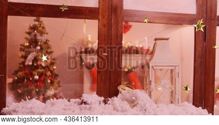 Image of glowing stars falling over christmas tree seen through window. christmas, tradition and celebration concept digitally generated image.