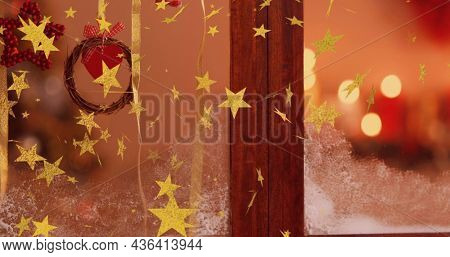Image of stars flying over christmas decorations in window. christmas christmas, tradition and celebration concept digitally generated image.