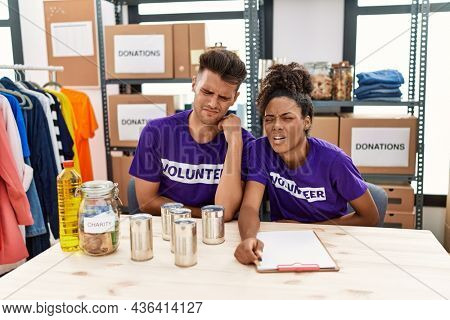 Young interracial people wearing volunteer t shirt at donations stand with hand on stomach because nausea, painful disease feeling unwell. ache concept.