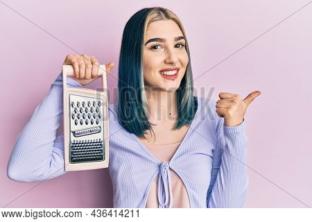 Young modern girl holding grater pointing thumb up to the side smiling happy with open mouth