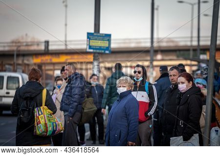 Belgrade, Serbia - February 28, 2021: Selective Blur On A Senior Old Woman In A Crowd Of People Wait