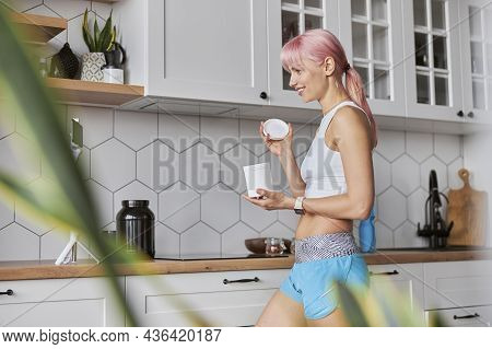 Cheerful Lady In Tracksuit Shows Open Jar Of Dietary Supplement To Camera In Kitchen