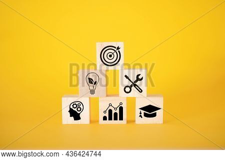 A Business Or Economic Growth Concept With Icons And Goals On Wooden Cubes On A Yellow Background. G