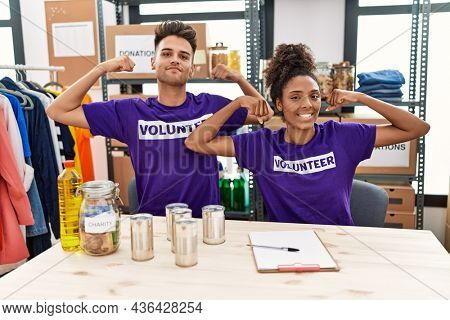 Young interracial people wearing volunteer t shirt at donations stand showing arms muscles smiling proud. fitness concept.
