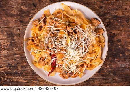 Portion Of Italian-american Pasta With Sausage Stew Sprinkled With Grated Cheese In A Plate On The T