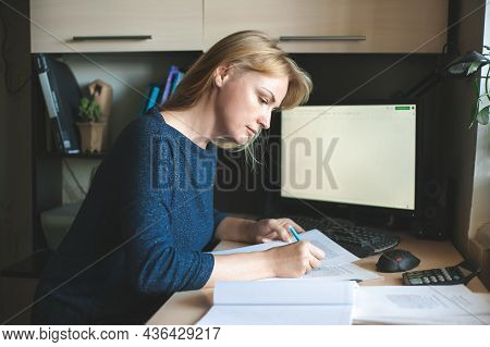A Blonde Woman About 40 Works From Home. Freelancer And Remote Work. A Woman Sits At A Table In Fron
