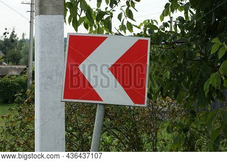 One Road Sign Turning Direction With Red  White Arrows In The Green Vegetation