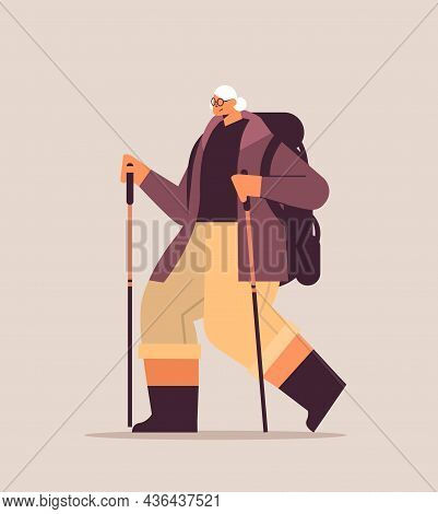Senior Woman Hiker Traveling With Backpack And Sticks For Walk Nordic Walking Active Old Age Concept
