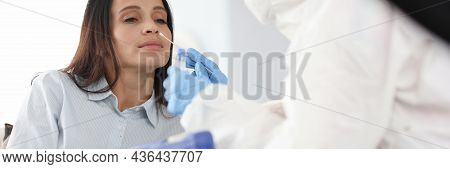 Doctor In Protective Anti-plague Overalls Taking Pcr Swab From Nose Of Woman Patient At Home