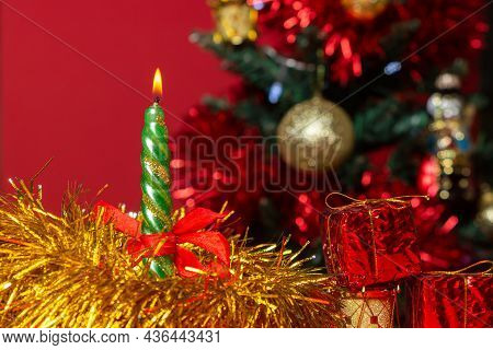 Christmas Concept. A Christmas Candle Burns Against The Background Of A Decorated Christmas Tree.