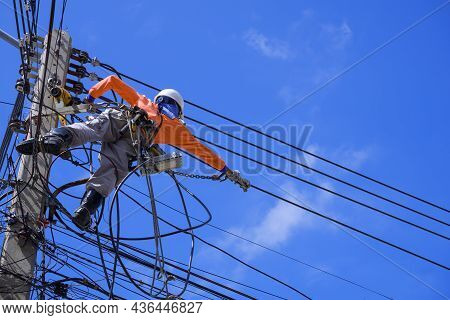 Low Angle View Of Electrician With Safety Equipment And Various Work Tools Is Installing Cable Lines