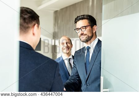 Group Of Cheerful Confident Business People Greeting With A Handshake At Business Meeting In Modern